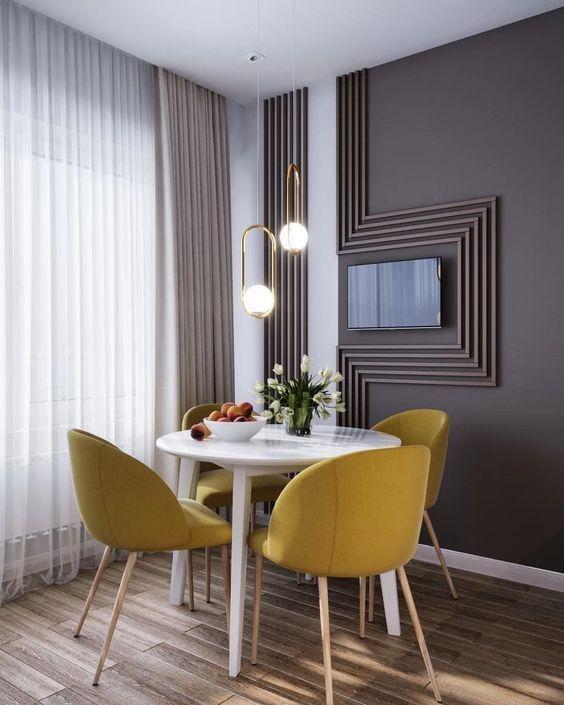 Sala de jantar moderna com paredes cinza, mesa redonda branca, cadeiras amarelas e piso de madeira.
