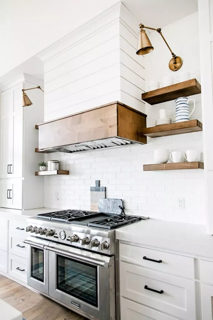 White shaker kitchen cabinets give a bright rustic feel to this open plan kitchen. Wood accents are used to bring a farmhouse feel to the space.