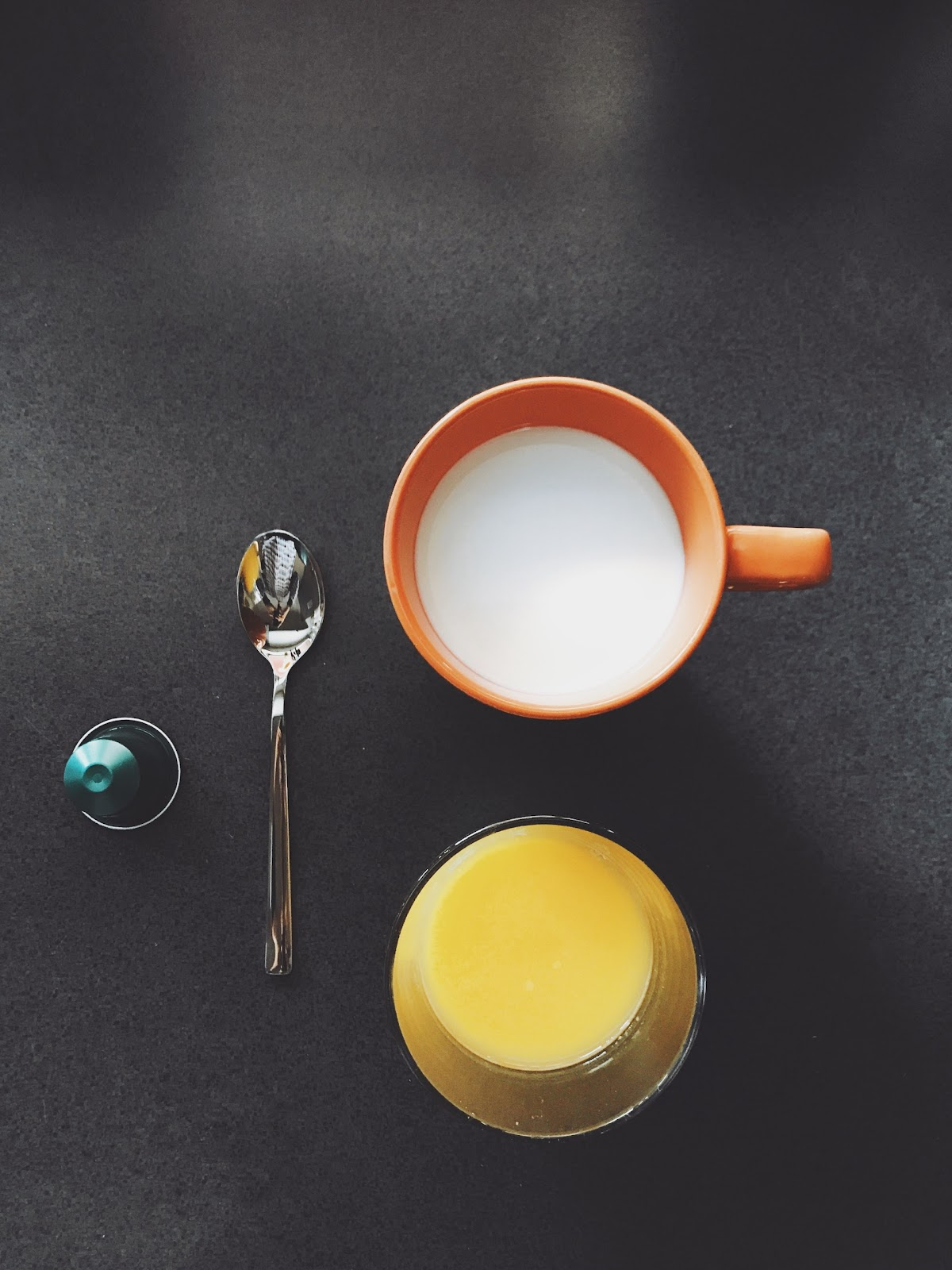 A glass of milk and a glass of juice sit on a table next to a spoon.