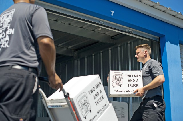 Two men and a truck employees putting boxes into a storage unit