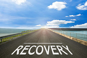 """A road with """"Recovery"""" written on it."""