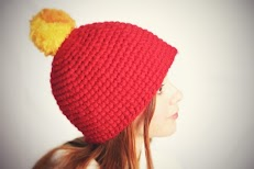 A girl wearing a Non itchy red acrylic pom pom Beanie.