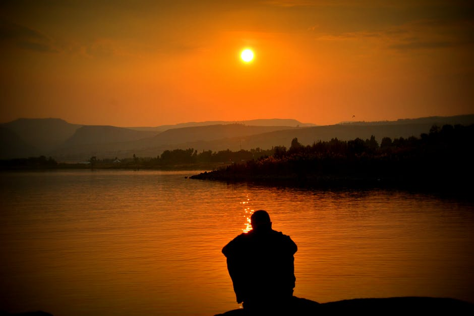 Silhouette of Person Sitting Beside Body of Water