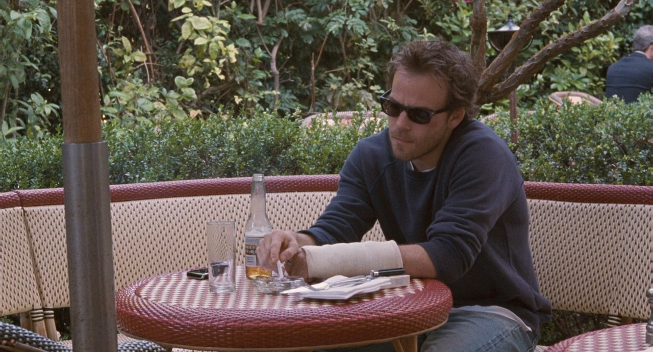 Johnny (Dorff), wearing blue jeans, a dark blue sweatshirt and sunglasses, is sitting by himself at an outdoor serving area while smoking and drinking beer. He is wearing his new white cast on his left arm, so far not a signature yet. He seems troubled about something as he has a deep frown on his face as he taps his cigarette on the restaurant's ashtray.