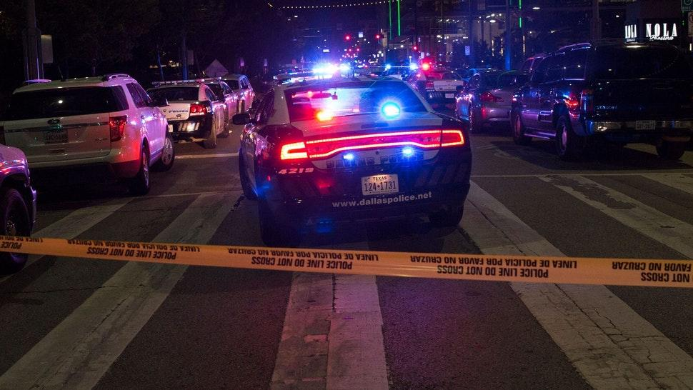 TOPSHOT - Police cars sit on Main Street in Dallas following the sniper shooting during a protest on July 7, 2016. - A fourth police officer was killed and two suspected snipers were in custody after a protest late Thursday against police brutality in Dallas, authorities said. One suspect had turned himself in and another who was in a shootout with SWAT officers was also in custody, the Dallas Police Department tweeted.