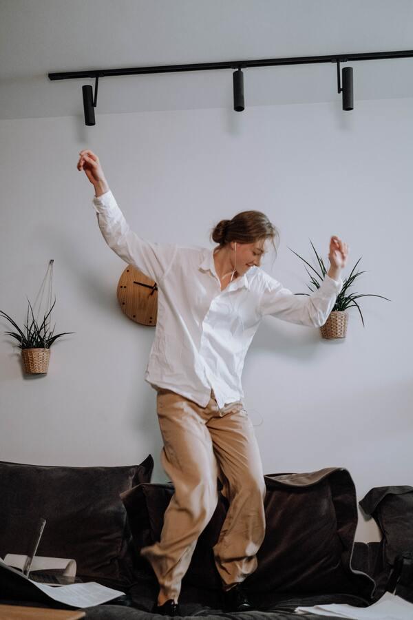 Uma mulher em cima do sofá dançando