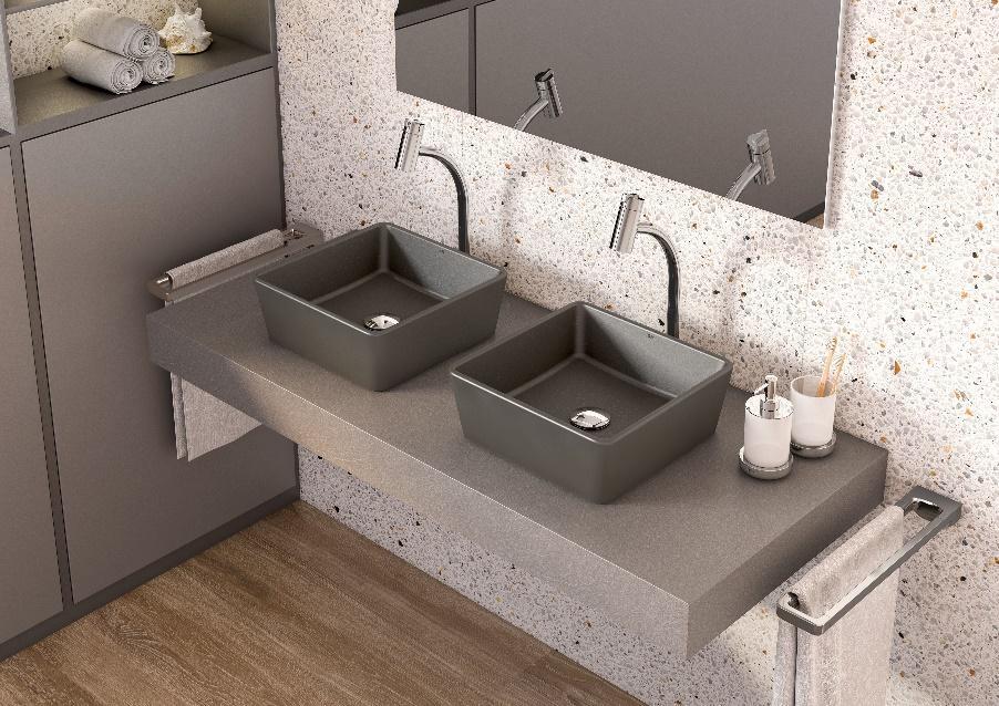 Banheiro com piso de madeira, bancada cinza com duas cubas cinza, parede revestida de granilite e armários cinza.