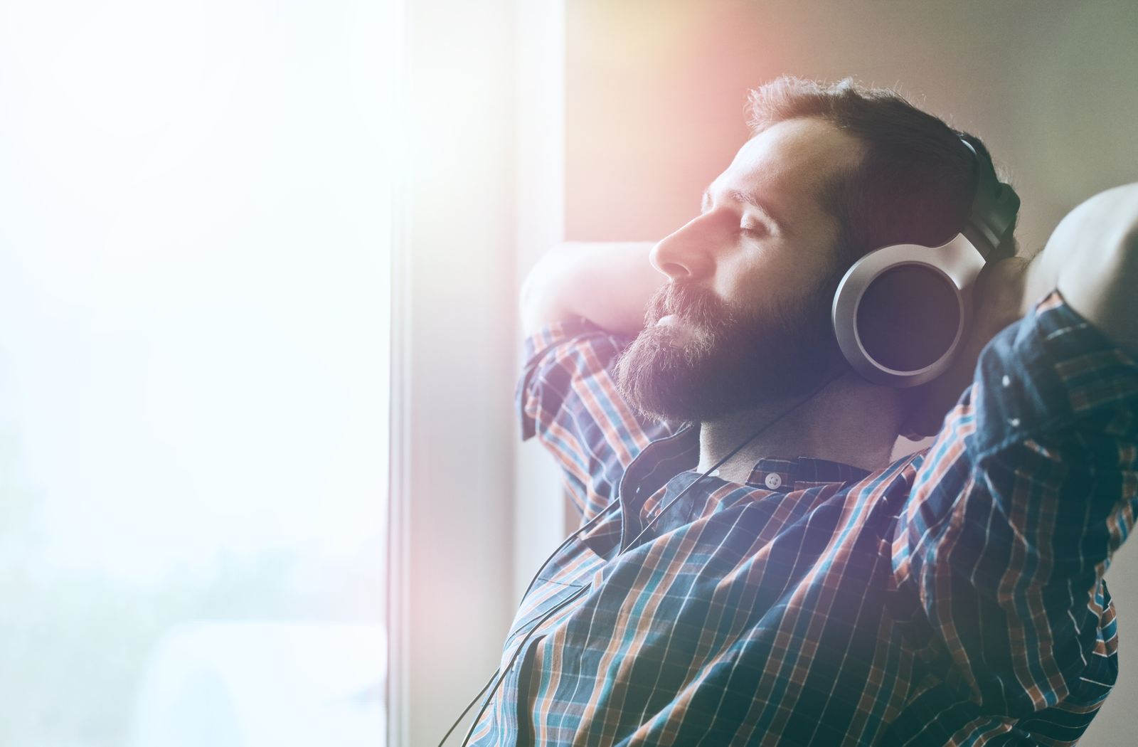 bearded man in a plaid shirt listening to music with headphones