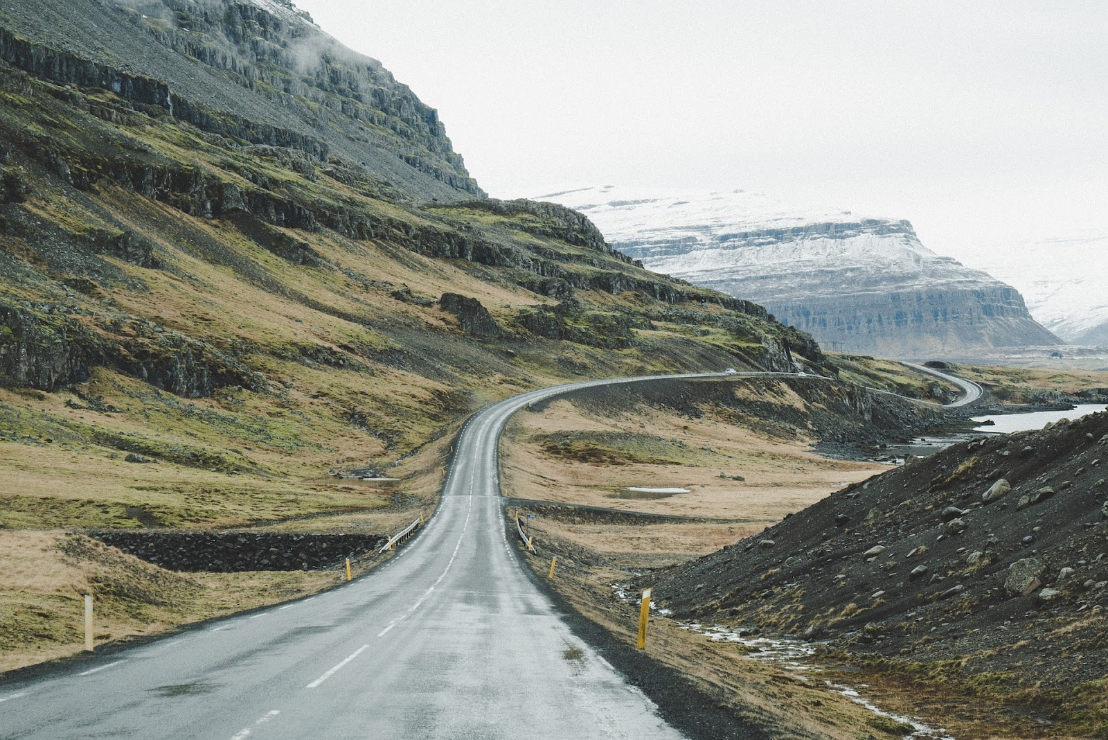 iceland ring road paved road uphill turns right and left across green fields on a wet cloudy day snow covered mountains in background