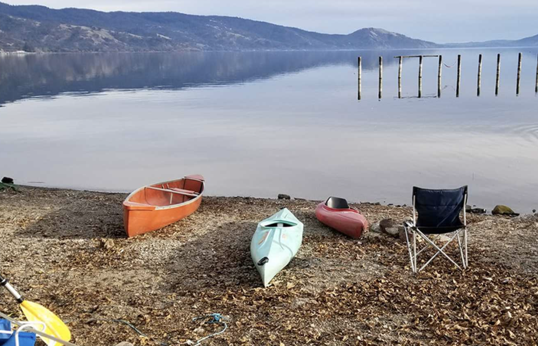 Kayaks and canoe next to water at The Aurora RV Park in California with mountain in the background