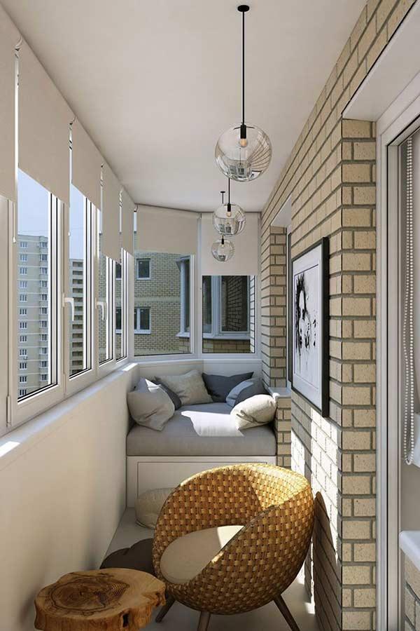 Varanda moderna com luminárias pendentes, parede de tijolinhos, banco planejado de estofado cinza com almofadas e cadeira de marrom.