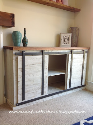 A DIY media console featuring sliding barn doors on the front