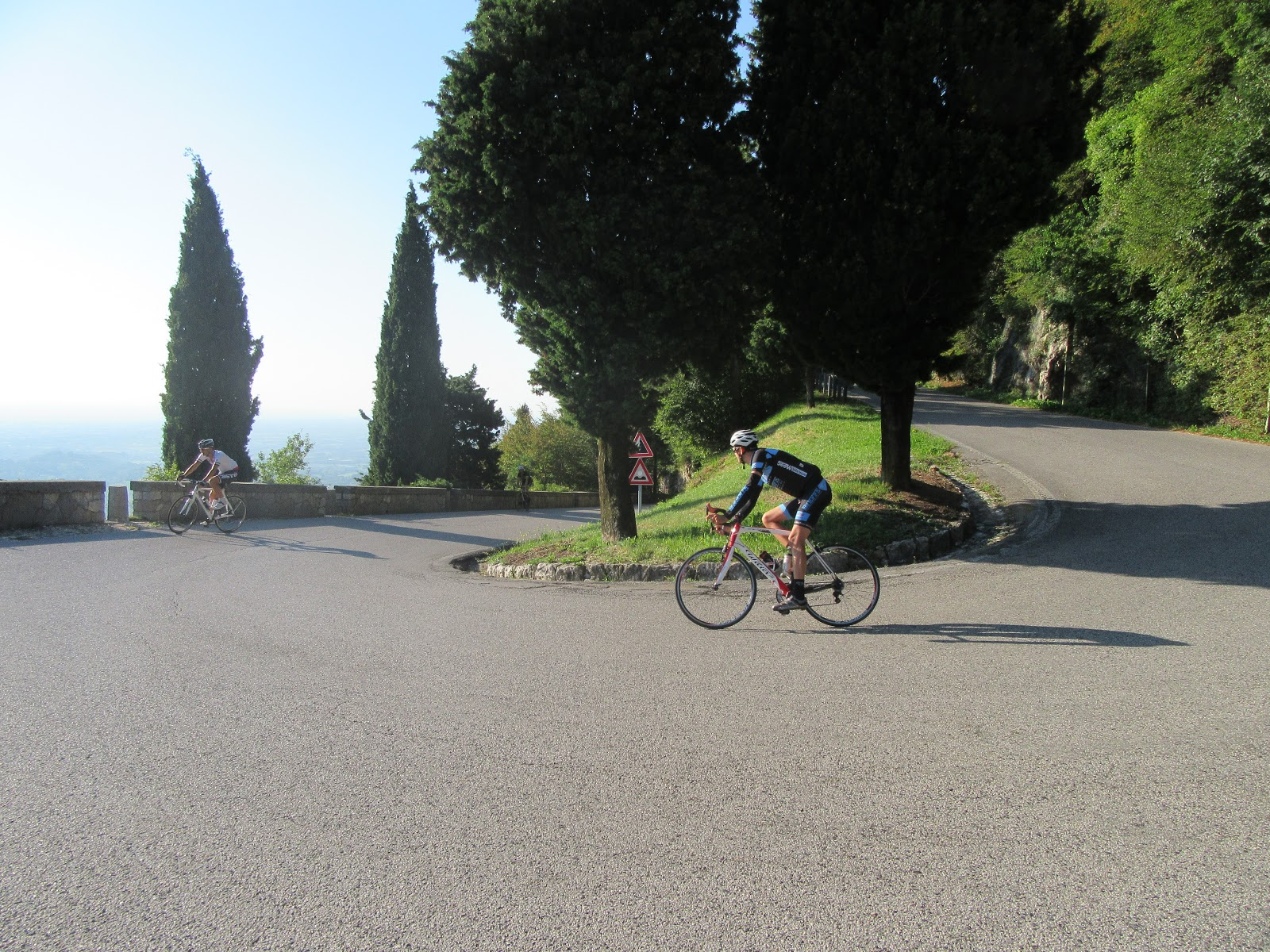 Climbing by bike Monte Grappa from Romano d'Ezzilino - tornante, cyclists and roadway