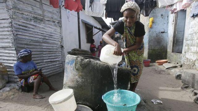 Жінка готується прати одяг у південноафриканських нетрях