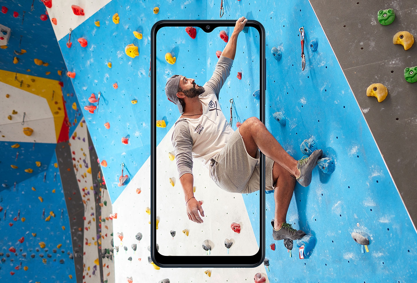 A man is doing rock climbing behind the frame of Galaxy M12.