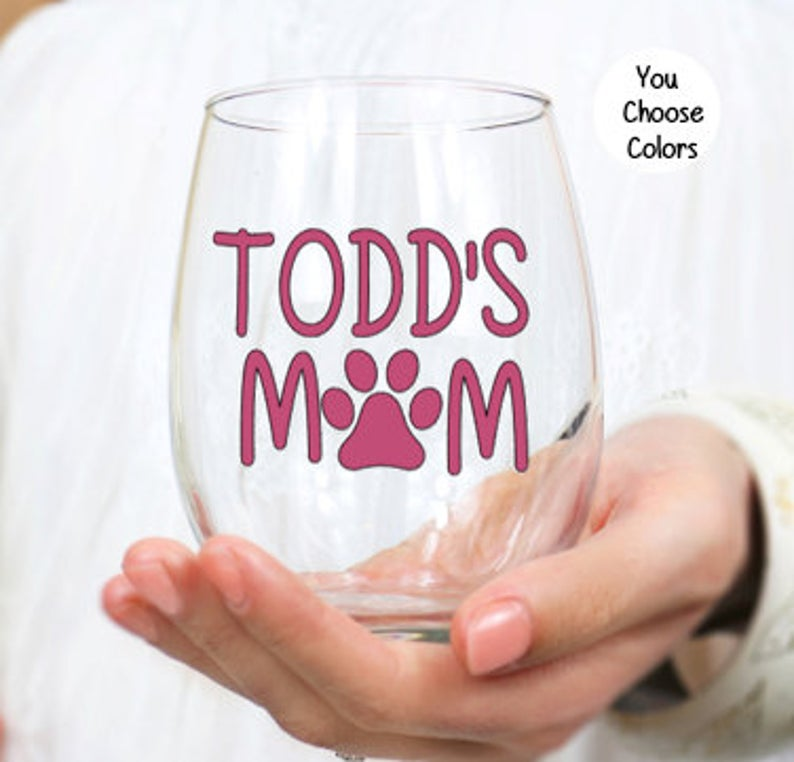 """stemless wine glass that says """"Todd's mom"""" on it. The O is a pawprint."""