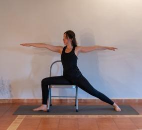 C:\Users\Sara\Documents\6. AUTÒNOMA\1. Ioga\1. Centres\3. Balancearte\Fotos Projecte Helena\Arxius petits\Retellades\1. Postures en peu\19.2 Virabhadrasana II amb cadira.jpg