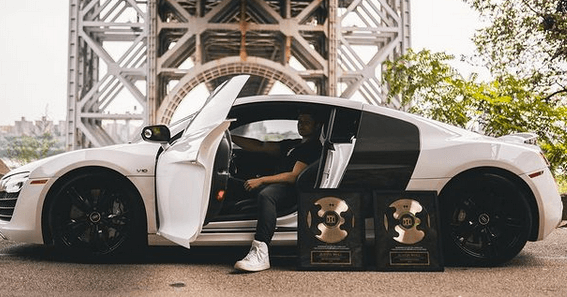 justin woll sitting in the seat of his white audi sports car with his 2 comma club click funnels awards leaning against the car