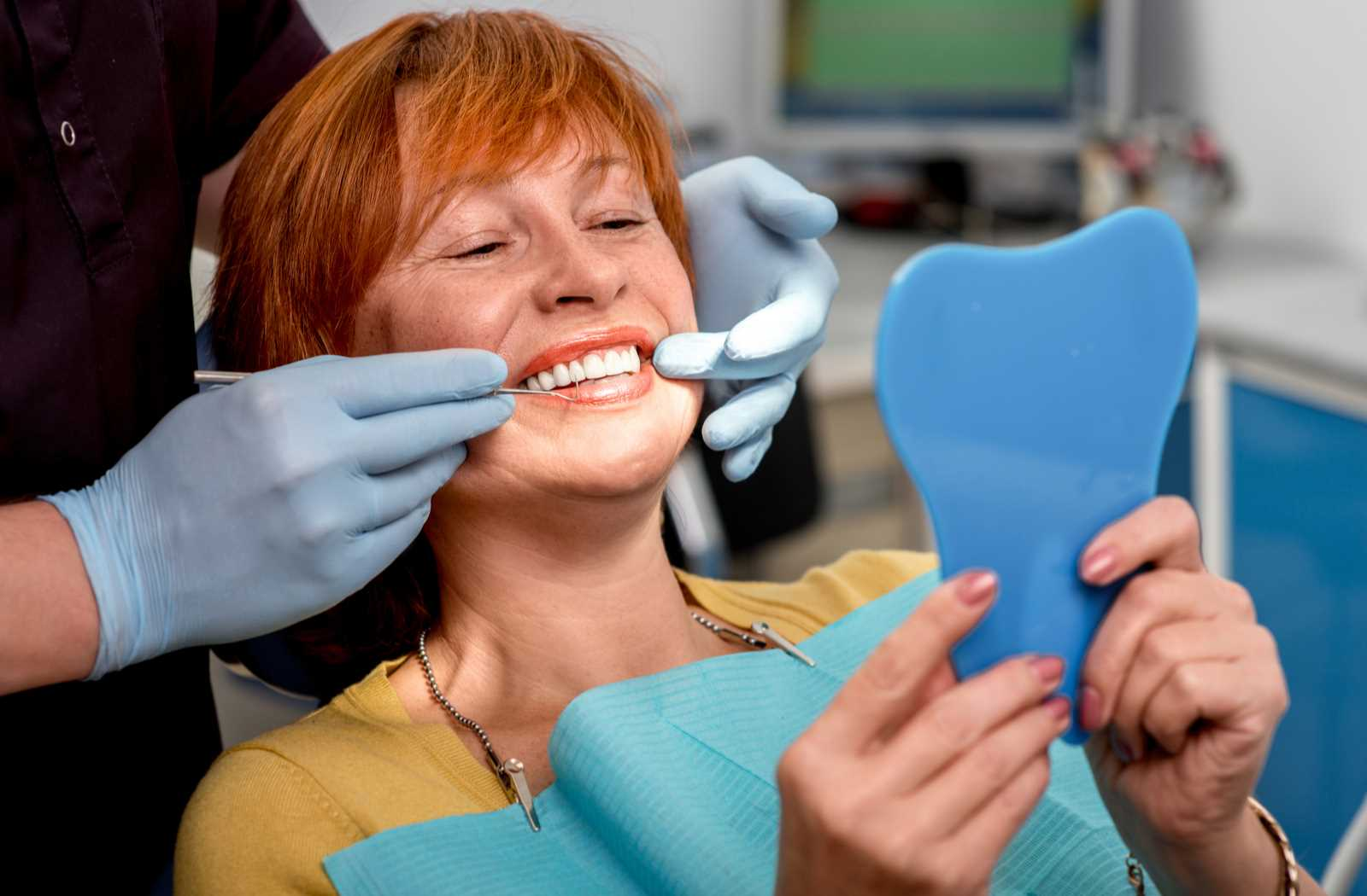 smiling woman in a chair looks at new dentures in a blue plastic mirror