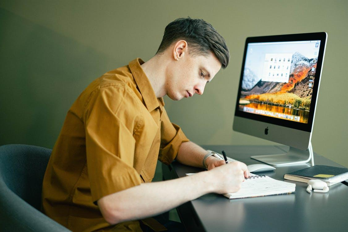 Man Taking Notes in front of his Computer