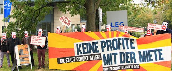 Protest vor der LEG-Verwaltung. Demonstranten mit Masken und Transparenten: »Keine Profite mit der Miete. Die Stadt gehört allen!«.
