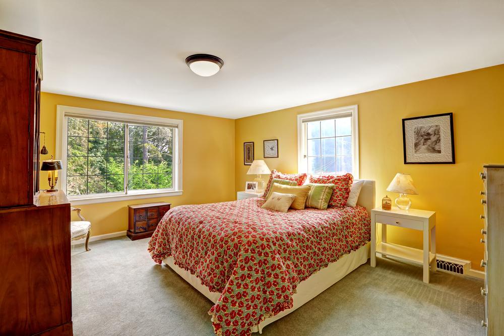 Um quarto com paredes amarelas e móveis de madeira.