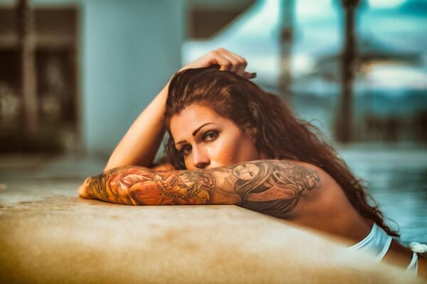 Mulher apoiada na beira da piscina com o braço coberto de tatuagens.