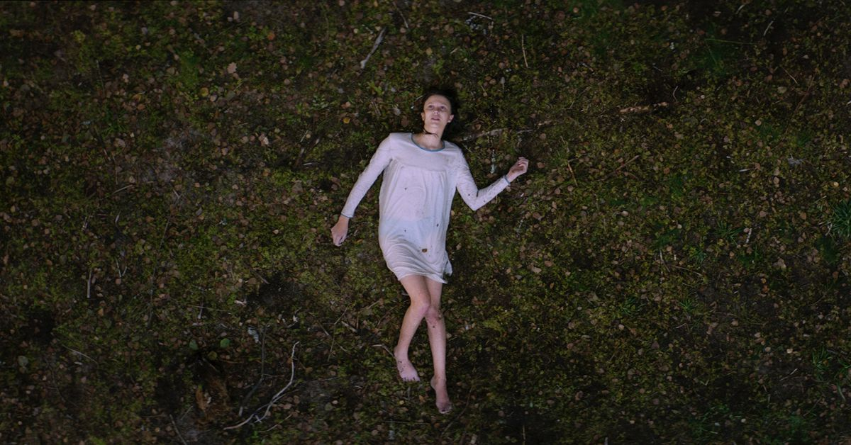 Thelma (2017). A distanced birds eye view shot of Thelma in a white night dress which is soaking wet, as is her hair. She is lying on a patch of grass outside, covered in bits of dirt and leaves, sprawled out like a corpse, but her eyes are open.