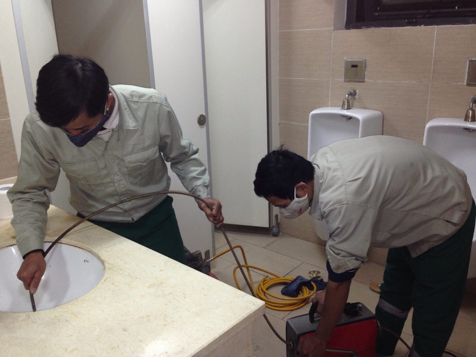 Nhân viên kỹ thuật đang xử lý thông nghẹt bồn rửa mặt