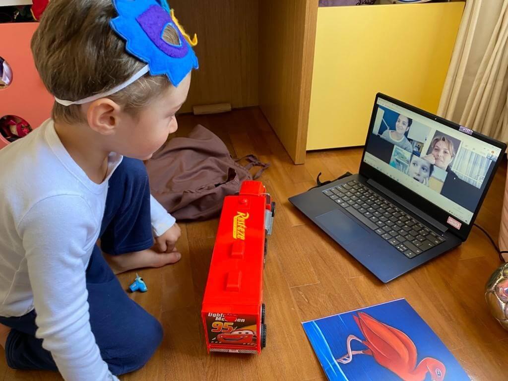A imagem mostra uma criança em frente a uma tela de computador.