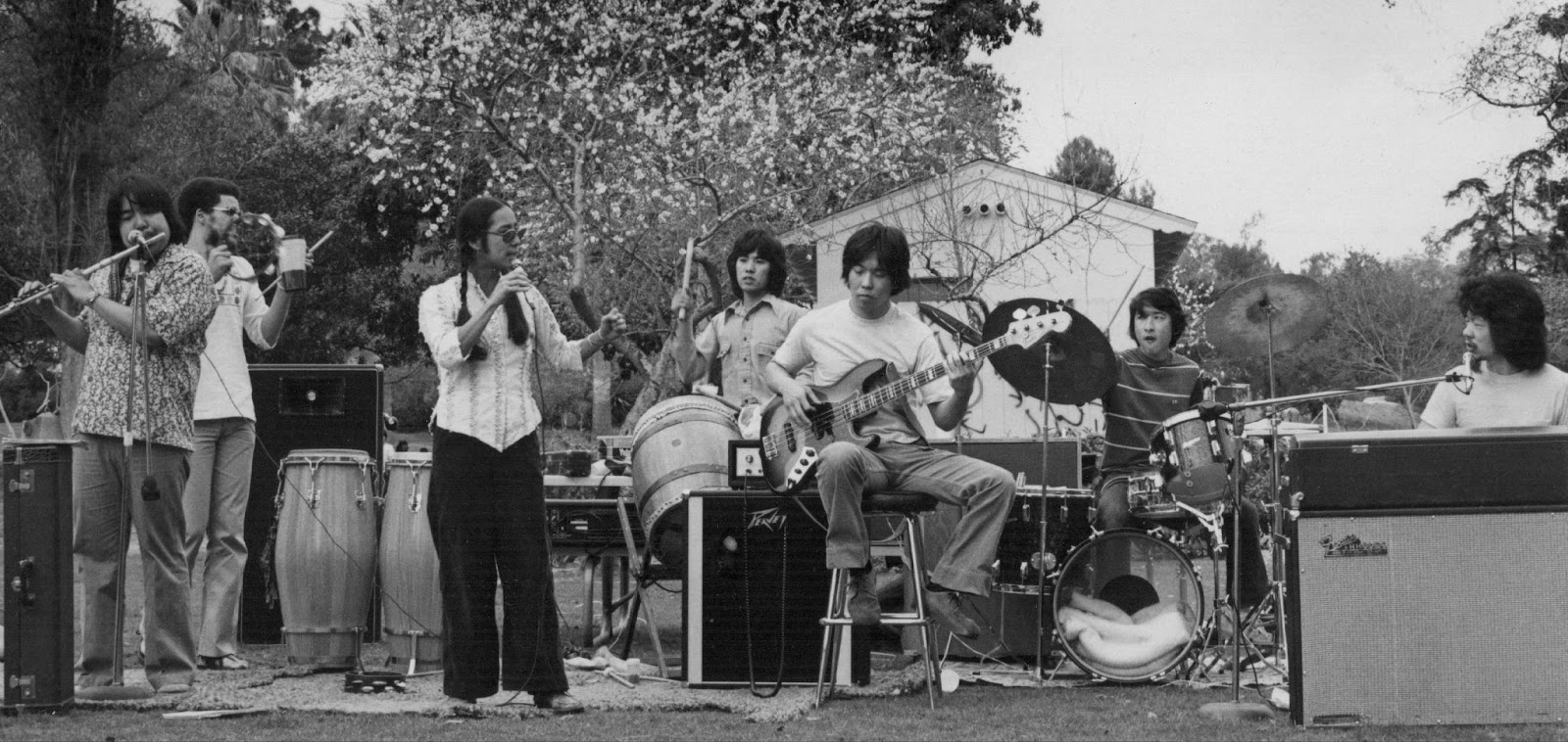 Warriors of the Rainbow band performing in Echo Park in 1978. An Asian American woman is singing into a microphone while five Asian American men and one Black man play instruments.