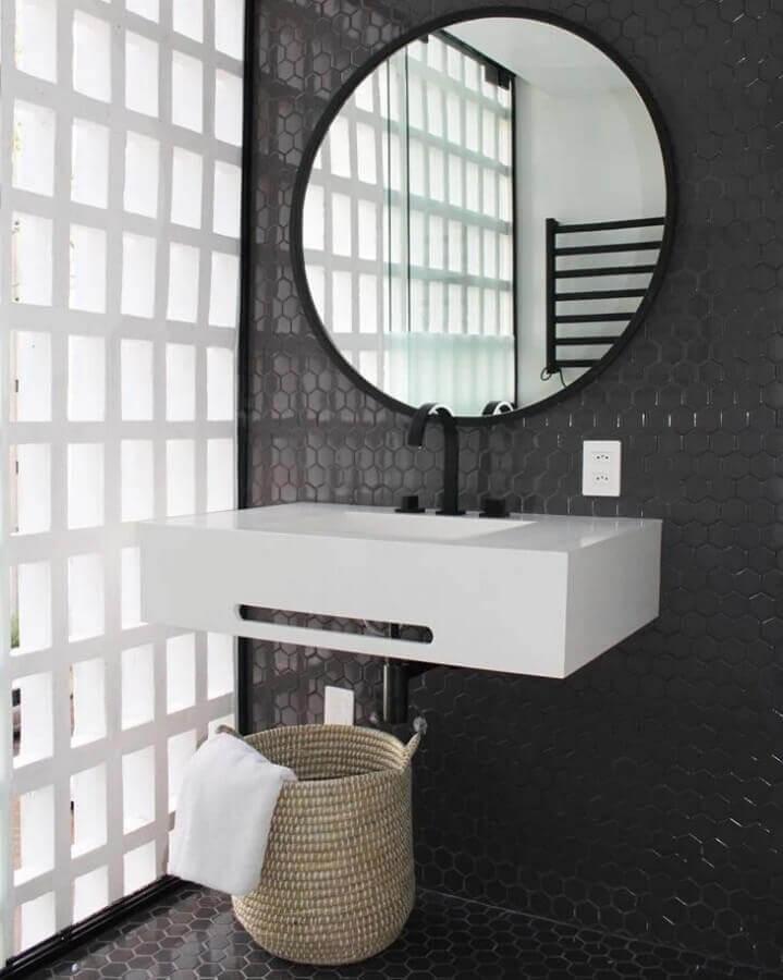 Banheiro com revestimento hexagonal preto em formato pequeno na parede e piso, cesto de palha no chão, pia branca com torneira preta e espelho redondo com moldura preta.