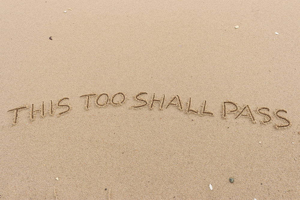 """""""this too shall pass"""" engraved on sand"""