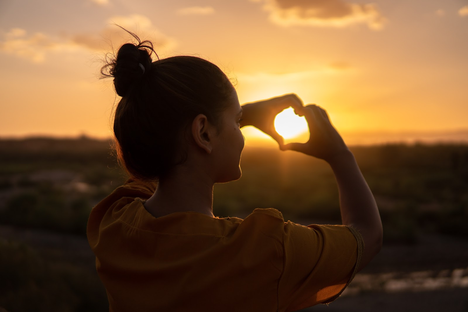 A girl looking at the sunrise in a positive mood