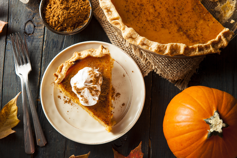 a slice of pumpkin pie on a plate with the cut pie and a whole pumpkin to the side and a small dish with spices