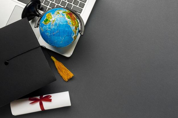 Vista superior do laptop com diploma e globo Foto gratuita