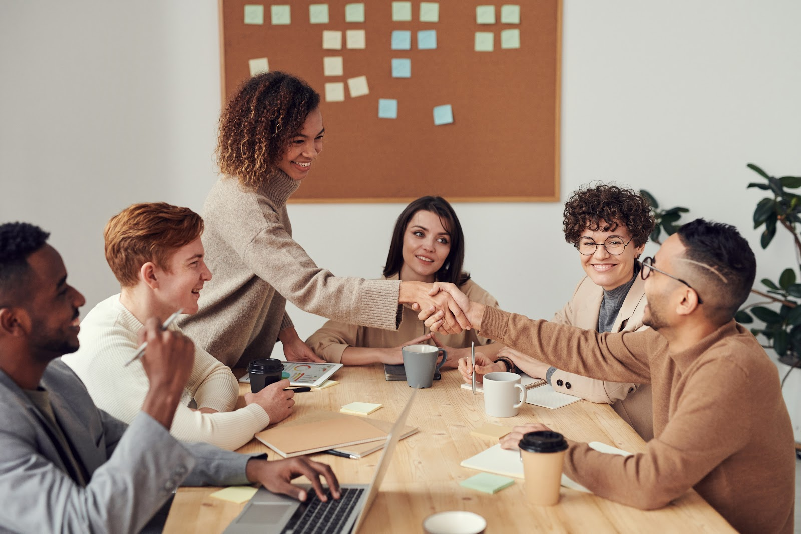 Rich results of employees sit around a boardroom table