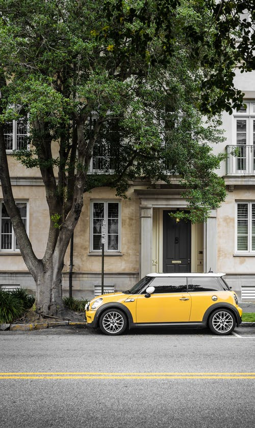 Yellow Mini Cooper Parked Beside White Concrete Building Leasing Vs Buying