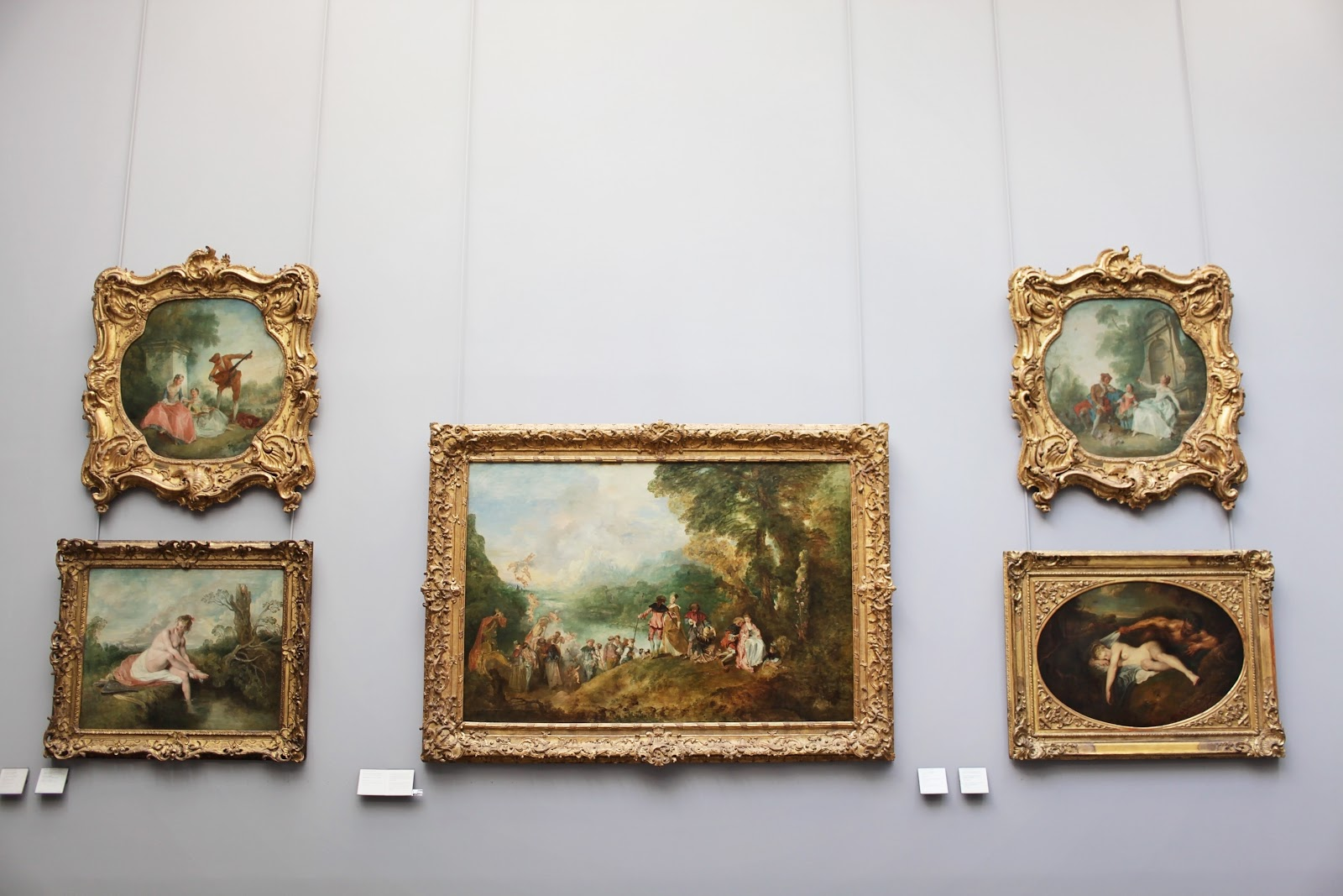 five paintings with ornate frames on a museum wall