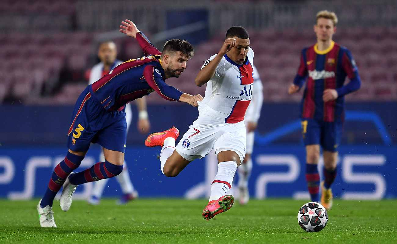 Gerard Piqué of Barcelona tugs on the shirt of PSG's Kylian Mbappé - Photo by David Ramos/Getty Images