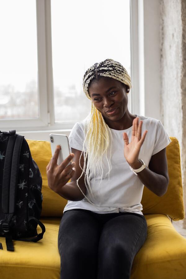 mulher negra sentada no sofá usando o celular