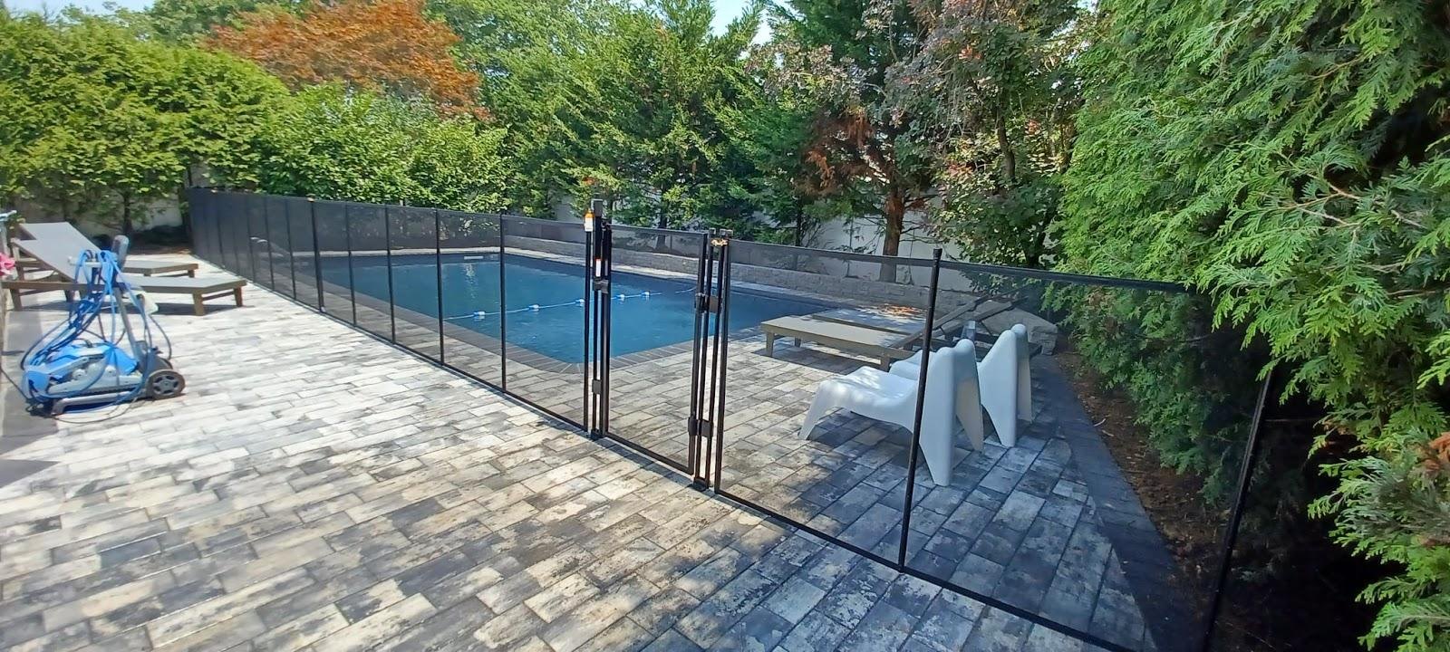 A mesh BABY-LOC fence is installed around an inground pool with a deck.