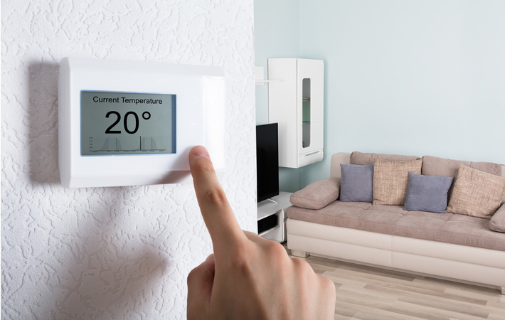 person adjusting a programmable thermostat