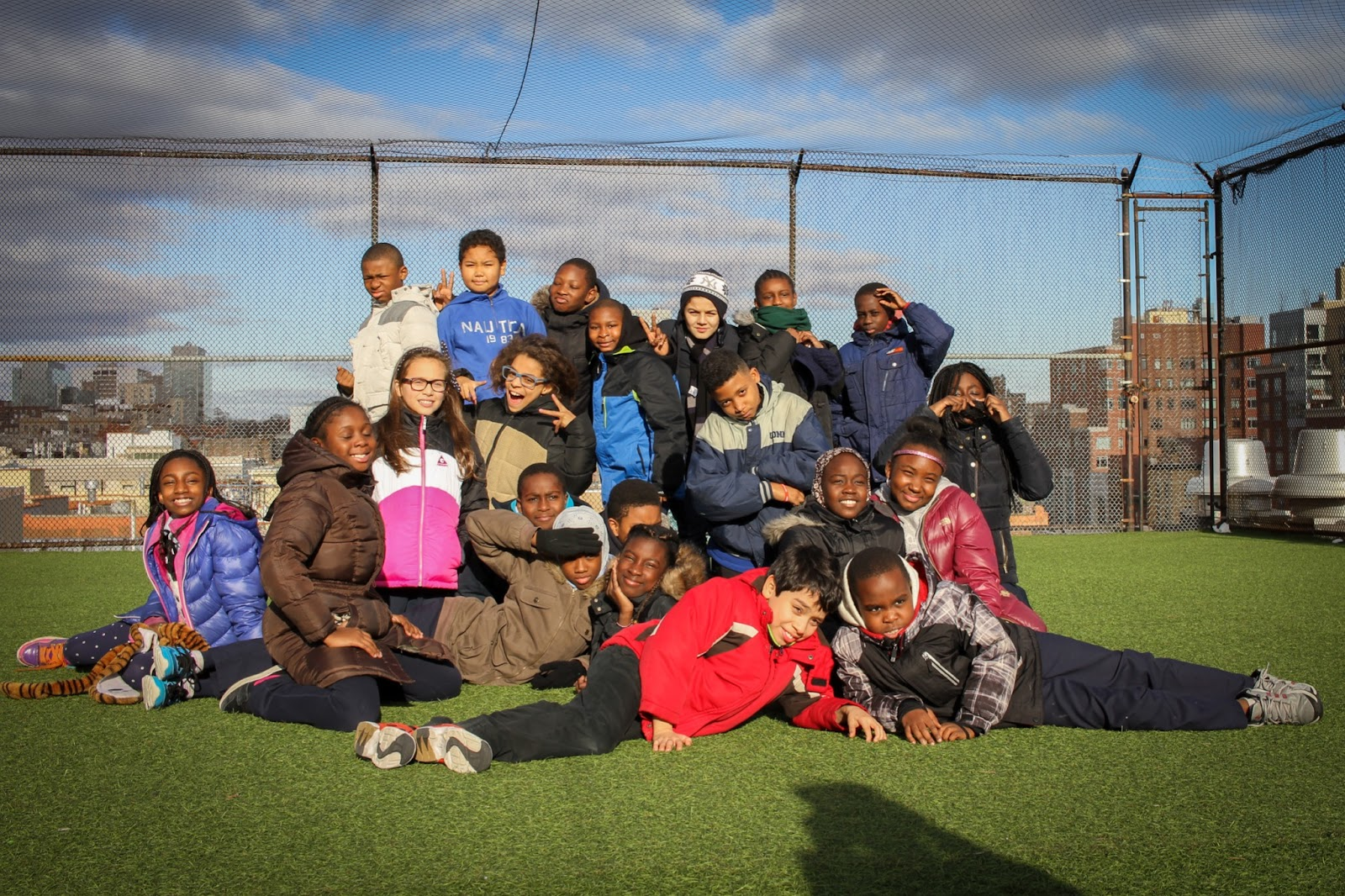 NYFACS students in winter jackets on rooftop overlooking Harlem