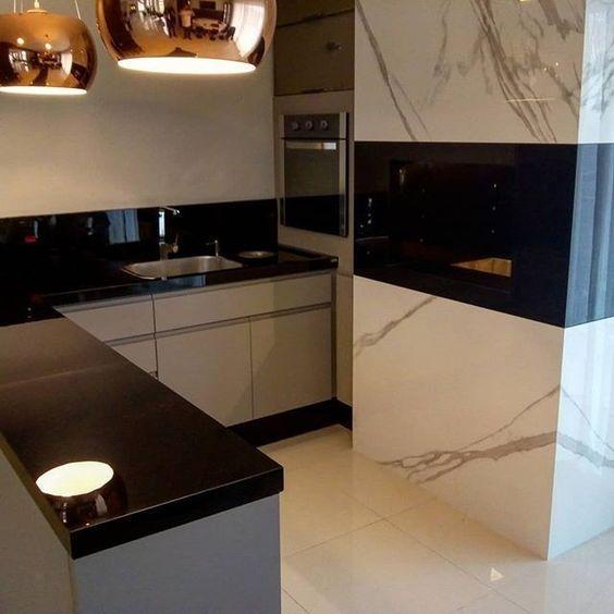 Area gourmet com churrasqueira revestida de porcelanato que reproduz mármore carrara branco, piso porcelanato branco e armário com bancada de mármore preta.