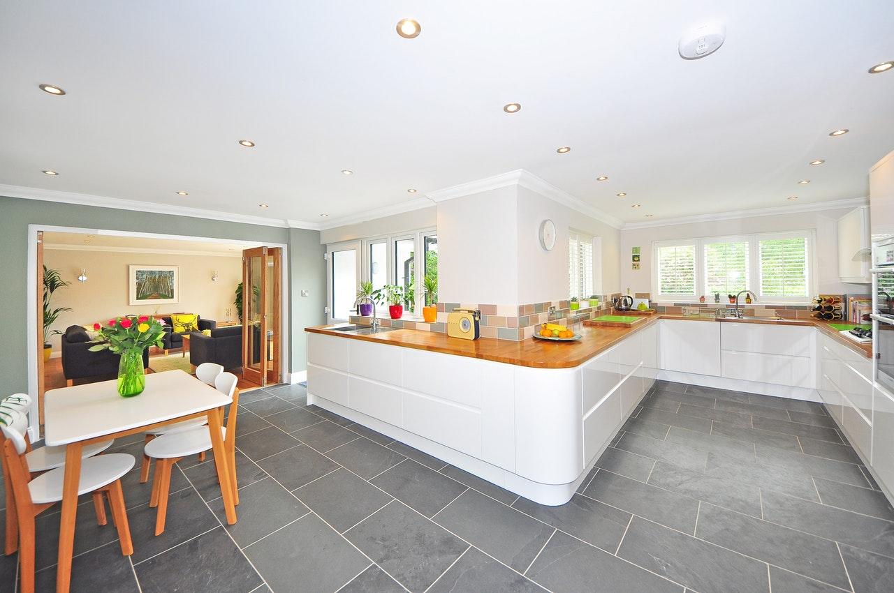 On open plan white kitchen with grey tiles and contrasting brown countertops