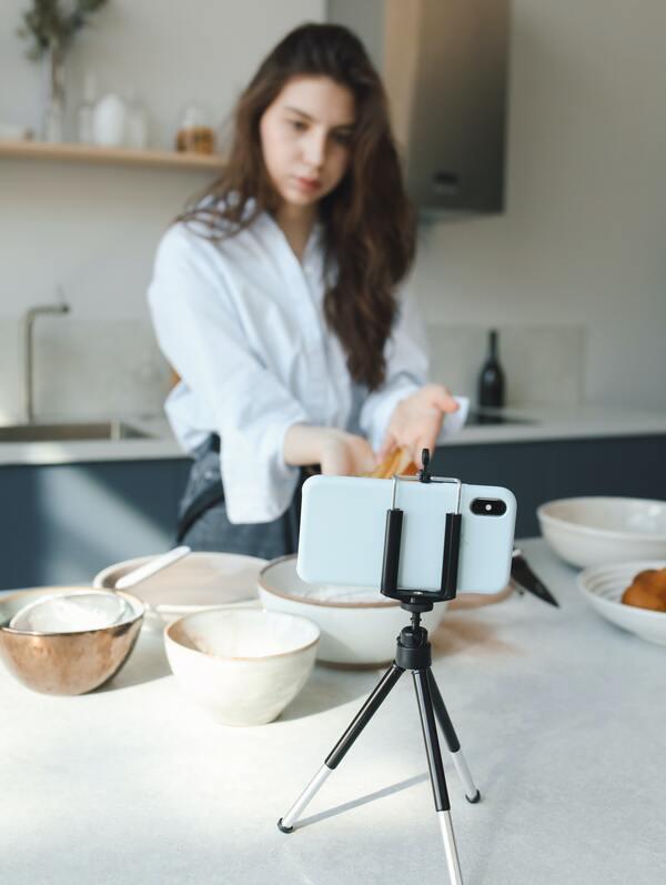 mulher cozinhando e filmando o passo a passo com o celular