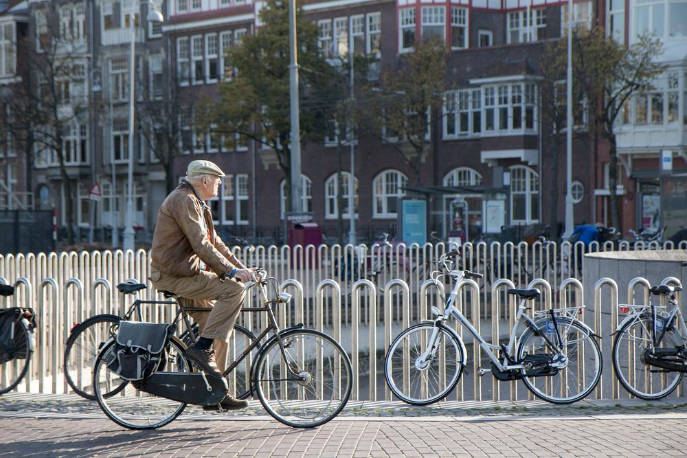 Idoso pedalando com bicicletas paradas ao fundo