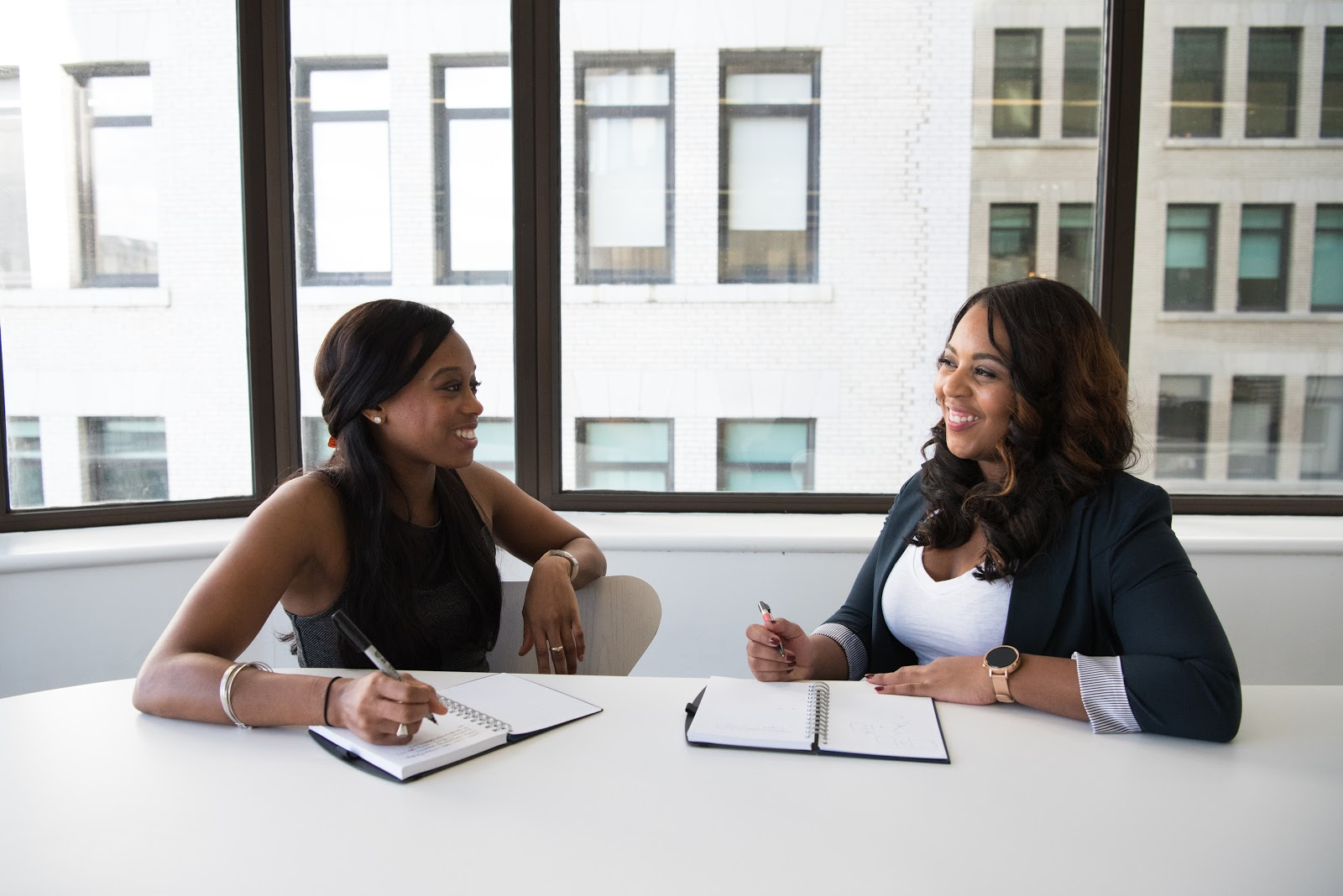 two women chat while at work in a tech office