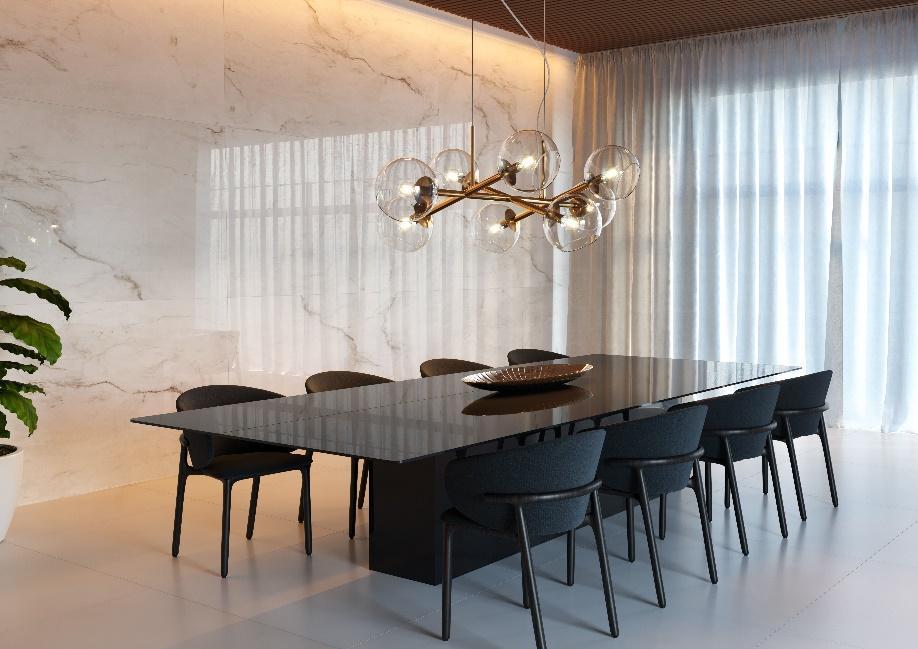 Sala de jantar com mesa preta com 9 cadeiras pretas, piso porcelanato branco, luminária pendente de bolas transparentes, parede com revestimento marmorizado branco e janela com cortina longa.